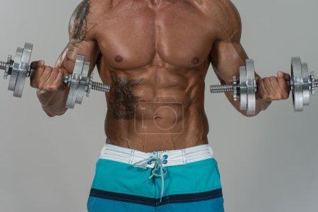 Bodybuilder Exercising Biceps With Dumbbells On Grey Background