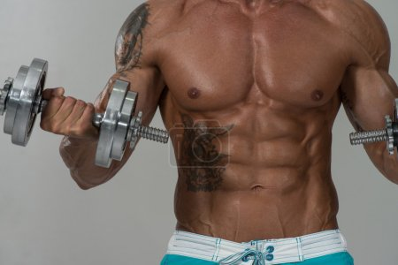 Mature Man Exercise With Dumbbells On Grey Background