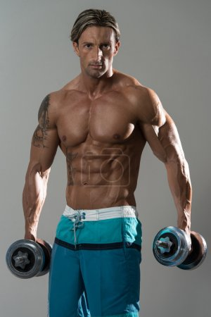 Portrait Of A Physically Fit Man With Dumbbells