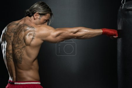 Photo for A Man With A Tattoo In Red Boxing Gloves - Boxing On Black Background - The Concept Of A Healthy Lifestyle - The Idea For The Film About Boxing - Royalty Free Image