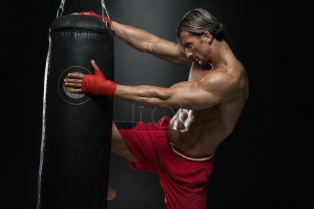 Mature Man Exercising Bag Boxing In Studio
