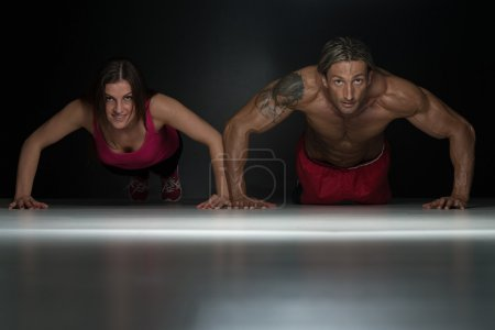 Photo for Couple Doing Pushups As Part Of Bodybuilding Training In A Studio - Royalty Free Image