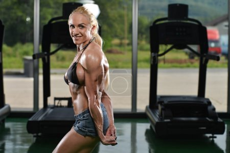 Photo for Serious Woman Bodybuilder Standing In The Gym And Flexing Muscles - Royalty Free Image