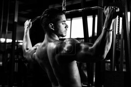Photo for Young Bodybuilder Doing Heavy Weight Exercise For Back In Gym - Royalty Free Image