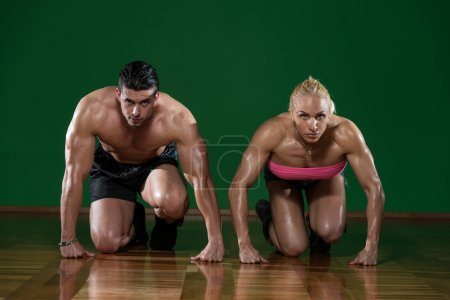 Strong Muscular Couple Kneeling On The Floor