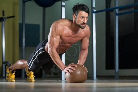 Young Man Exercising Push Ups On Medicine Ball