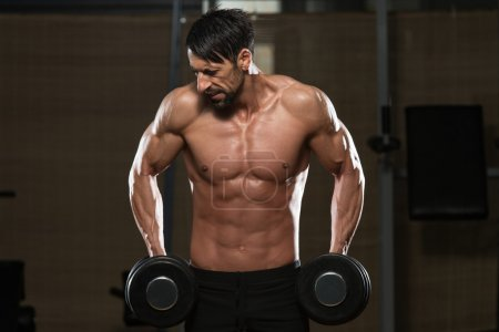 Bodybuilder Exercising Trapezius With Dumbbells
