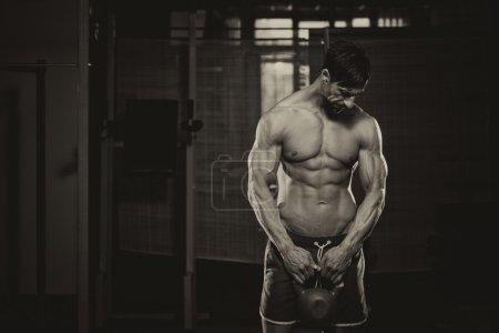 Photo pour Entraînement homme athlétique avec bell bouilloire - image libre de droit