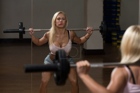 Photo for Young Woman Performing Barbell Squats - One Of The Best Body Building Exercise For Legs - Royalty Free Image
