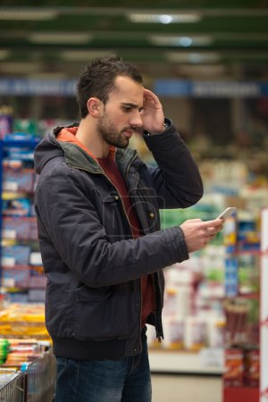 Man Looking Confused At Mobile Phone In Supermarket