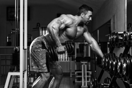 Photo pour Mexican Bodybuilder Doing Heavy Weight Exercise For Back With Dumbbells - image libre de droit