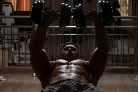 Bodybuilder Doing Exercise For Chest With Dumbbells
