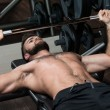 Постер, плакат: Young Man Doing Exercise For Chest With Barbell