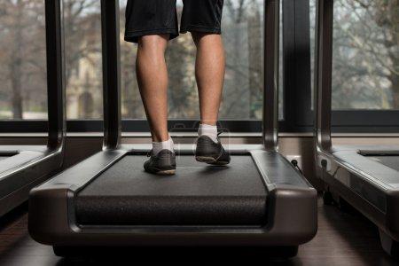 Photo pour Gros plan des pieds mâles courir sur tapis de course - flou de mouvement - image libre de droit