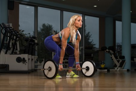 Mature Woman Exercising Back With Barbell