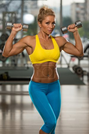 Mature Woman Exercising Shoulders With Dumbbells
