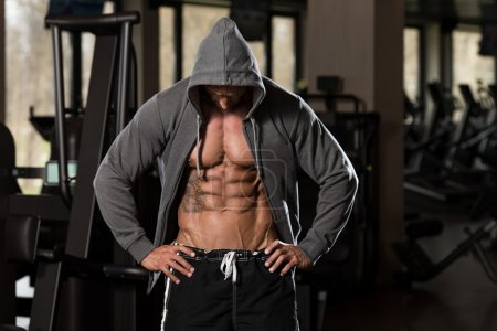 Photo for Portrait Of A Physically Fit Man In Hoodie - In Modern Fitness Center - Showing His Six Pack - Royalty Free Image