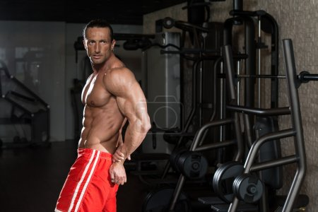 Muscular Mature Man Performing Side Triceps Pose