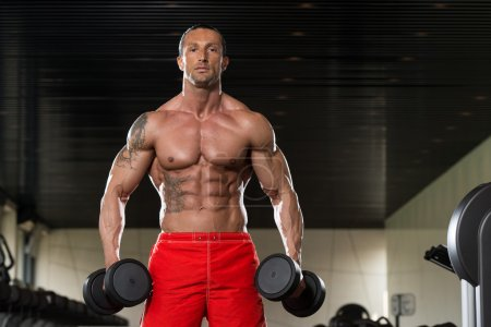 Photo for Muscular Mature Man Doing Heavy Weight Exercise For Biceps With Dumbbells In Modern Fitness Center - Royalty Free Image