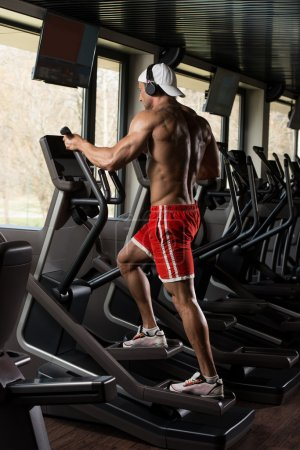 Photo for Muscular Mature Man Doing Aerobics Elliptical Walker In Modern Fitness Center - Royalty Free Image