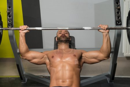Muscular Man Doing Bench Press Exercise For Chest