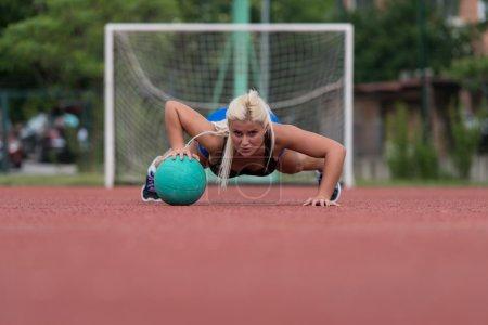 Photo pour Young Woman Outdoors Performing Push Ups On Medicine Ball Bodybuilding Exercise - image libre de droit