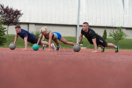 Photo pour Un groupe de jeunes dans la classe d'aérobic exécutant des pompes sur l'exercice de boule de médecine en plein air - image libre de droit