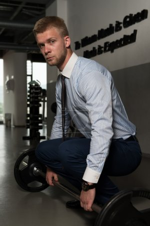 Healthy Young Businessman Doing Exercise For Back