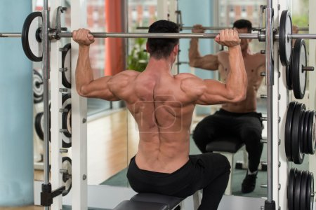 Male Bodybuilder Doing Heavy Weight Exercise For Shoulders