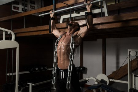 Healthy Man Doing Exercise For Back With Chain