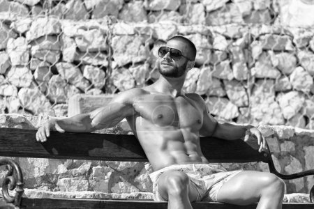 Smiling Athlete With Naked Torso Sitting And Resti...