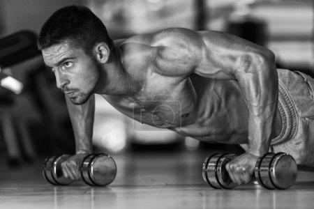 Photo for Young Athlete Doing Pushups With Dumbbells As Part Of Bodybuilding Training - Royalty Free Image