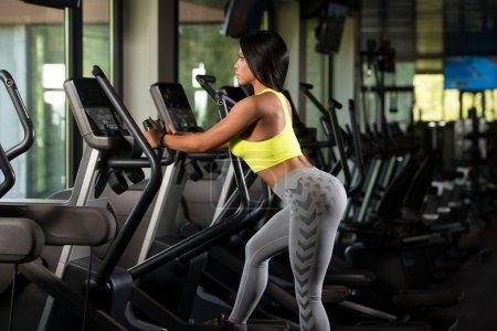 Latino Women On Elliptical Treadmill In Fitness Gym
