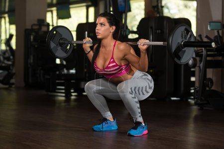 Photo pour Jeune femme mexicaine travaillant jambes avec Barbell dans le centre de remise en forme - Squat - image libre de droit