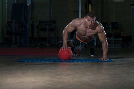 Photo pour Jeune adulte athlète faisant Push Ups sur médecine-ball dans le cadre de la formation de culturisme - image libre de droit
