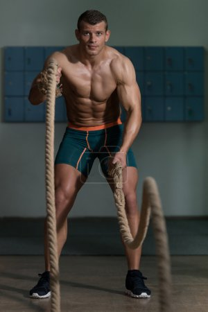 Young Man Battling Ropes At Gym Workout Exercise
