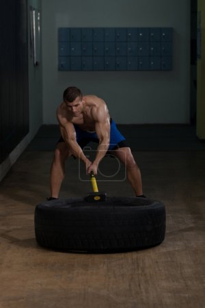 Workout At Gym With Hammer And Tractor Tire