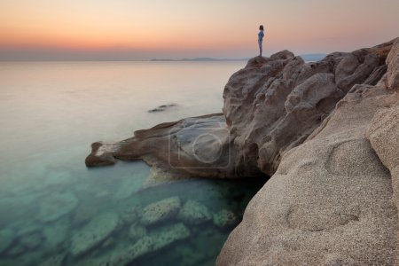 Photo for Lone woman standing on an edge of cliff and watching the rising sun from the shore with strange rocks. Long exposure shot in Aegean Sea, Greece. - Royalty Free Image