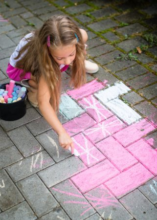 child drawing with colorful chalks