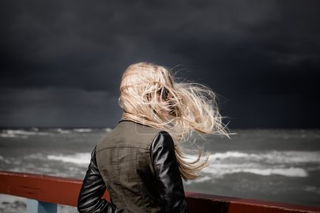 Photo for Blond girl looking at stormy sea. Dark sky in background. Selective focus - Royalty Free Image