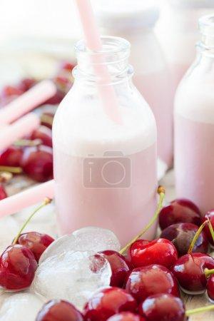 Photo pour Milk-shake crémeux aux cerises fraîches sur glaçons froids - image libre de droit