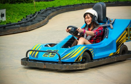 Cute Asian Thai girl is driving Go-kart car with speed in a playground racing track. Go kart is a popular leisure motor sports.