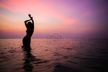 Beautiful sporty feminine silhouette. evening swimming