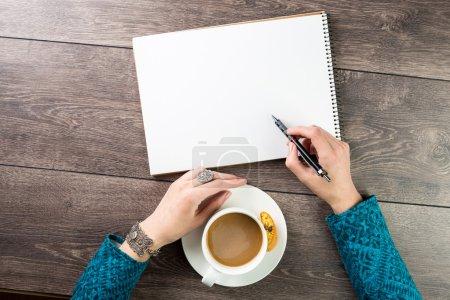 Photo pour Top vue mains et bloc-notes sur la table - image libre de droit