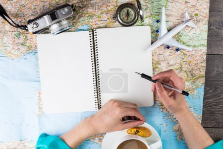 Woman is sitting at the table over the map.
