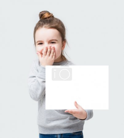 Photo for Giggles happy kid girl closes face with her hand. Confused little girl holding a poster for your information. Gray background - Royalty Free Image