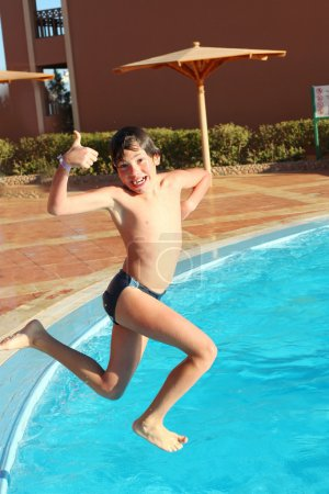 preteen boy jump into the open air swimming pool