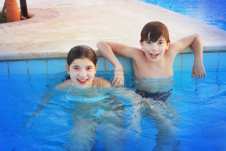 siglings boy and girl play in open air swimming pool at the egyp