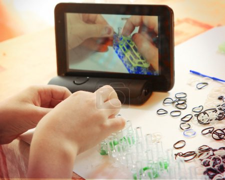 Hand make rainbow loom toy with online lesson on tablet computer
