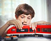 Nedospělý hezký boy hrát s hračky meccano vlaku a železniční sta